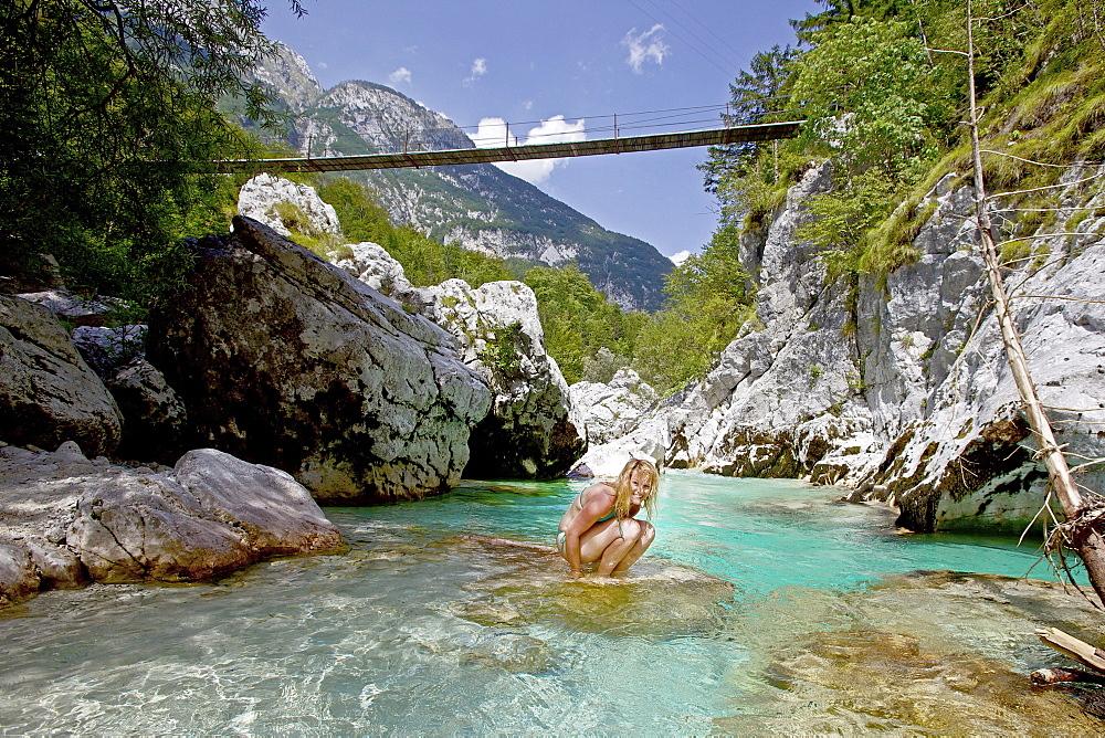Young woman sitting in the river Soca, Alpe-Adria-Trail, Tolmin, Slovenia - 1113-104379