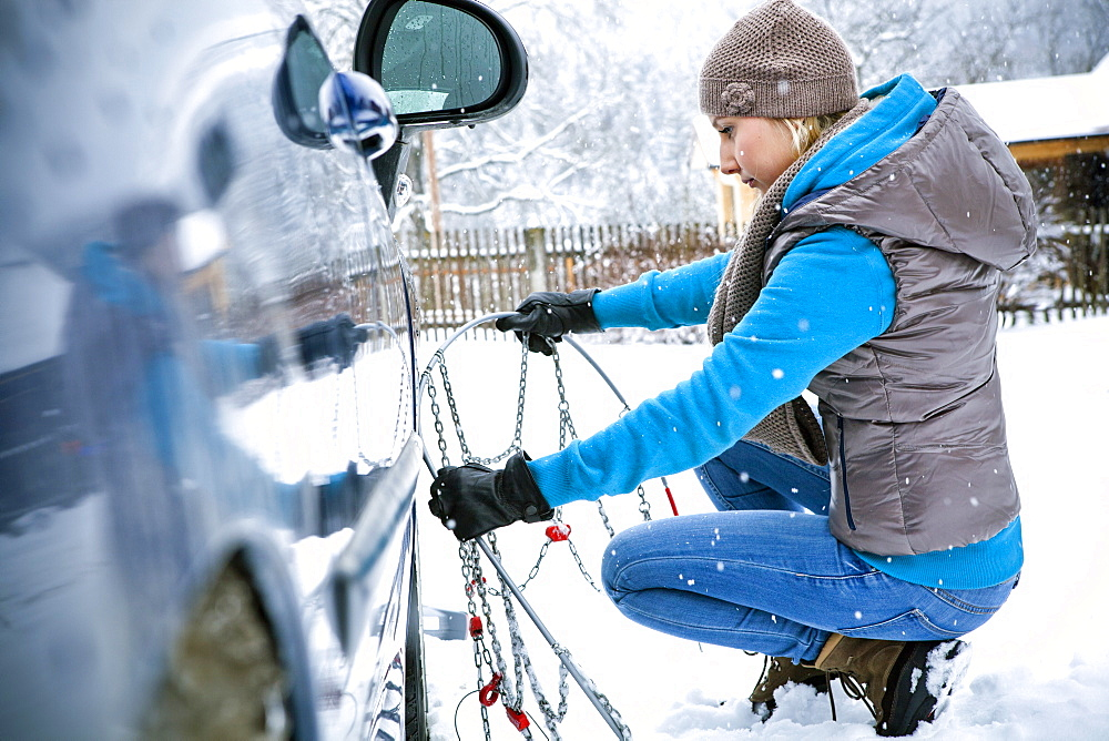 Woman applying chain to tire in snow, Styria, Austria - 1113-104392