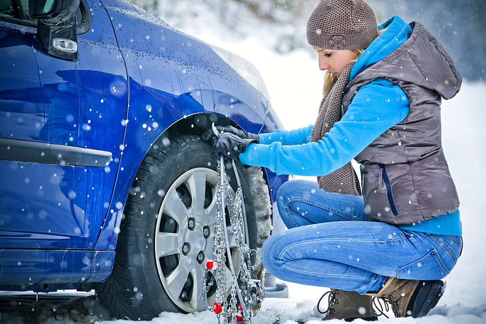 Woman applying chain to tire in snow, Styria, Austria - 1113-104393