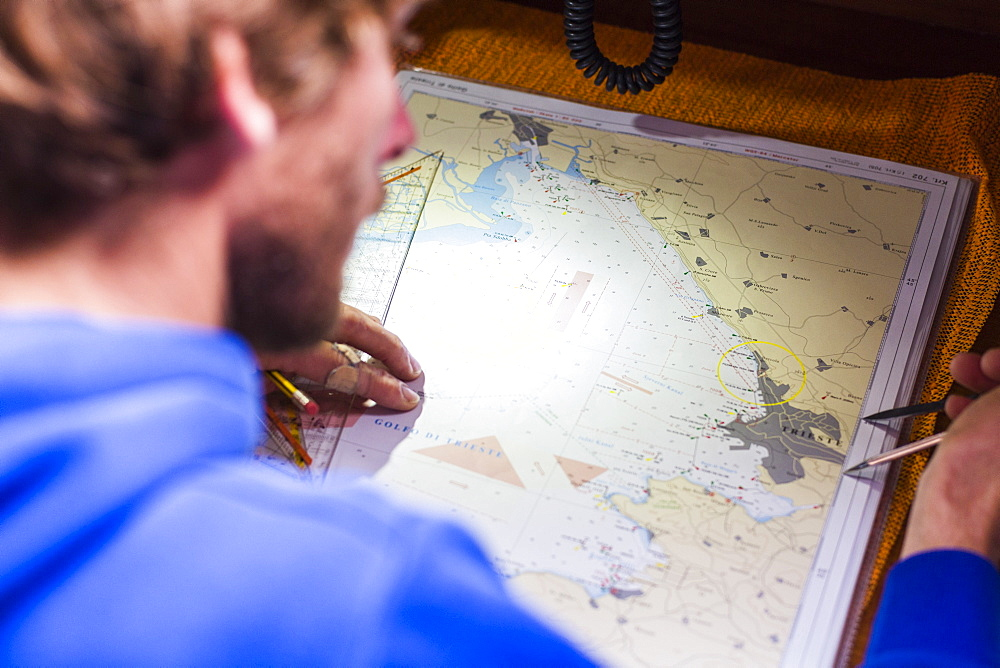 Skipper planing a route on a nautical chart at a sailing boat, Pula, Istria, Croatia - 1113-104460
