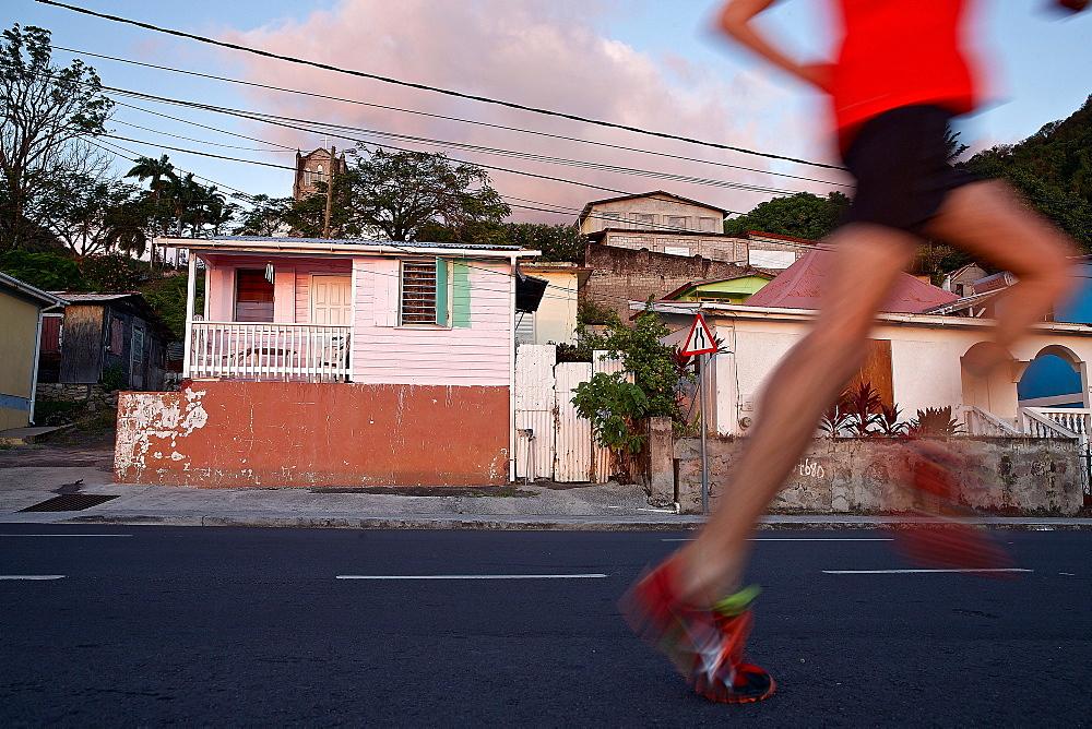 Young man running along a street, Dominica, Lesser Antilles, Caribbean - 1113-104800