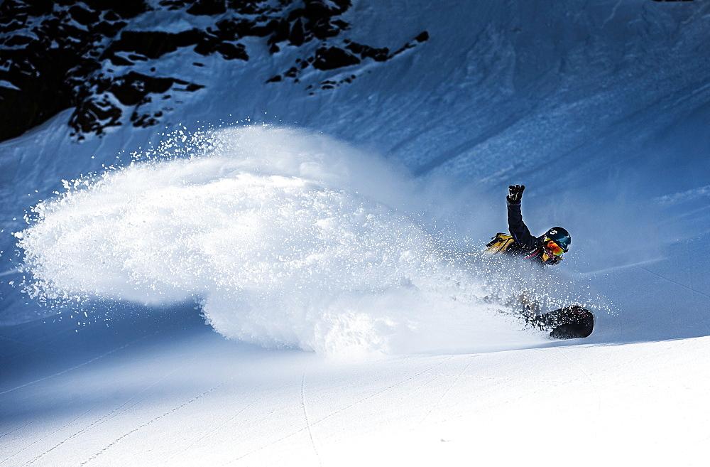 Young female snowboarder riding through deep powder snow in the mountains, Pitztal, Tyrol, Austria - 1113-104820