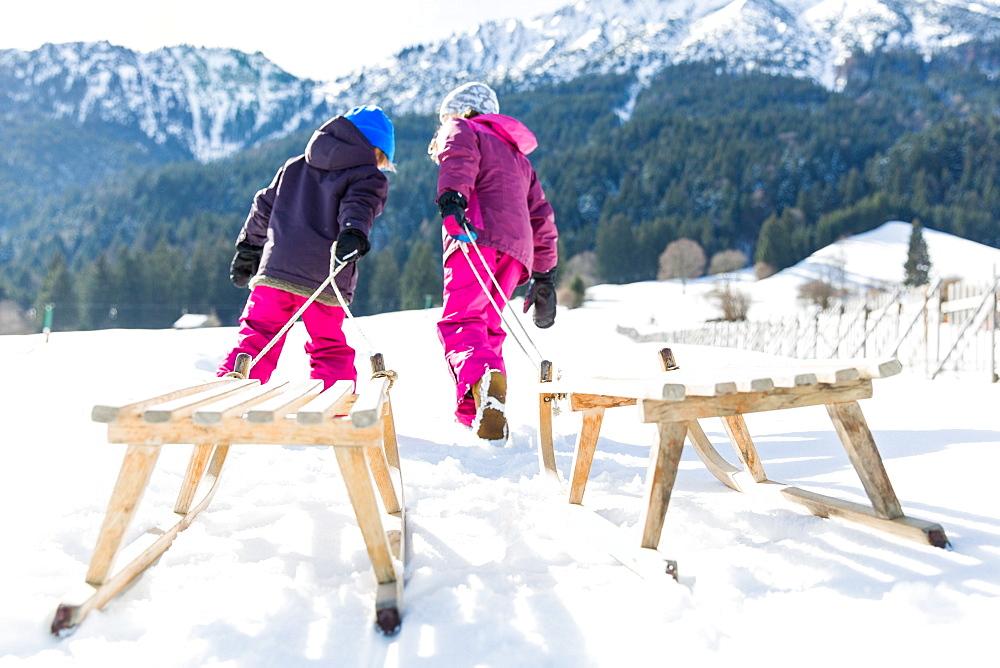 girl and boy pulling their sledges, Pfronten, Allgaeu, Bavaria, Germany - 1113-105047