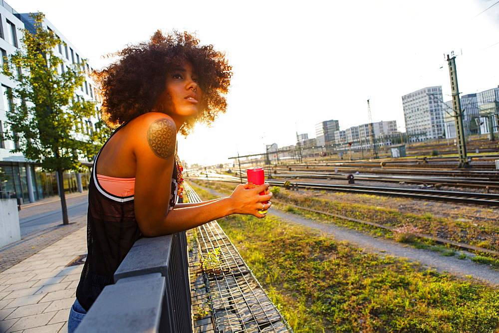 Young afro-american woman relaxed in urban scenery with backlight, Hackerbruecke Munich, Bavaria, Germany - 1113-105139
