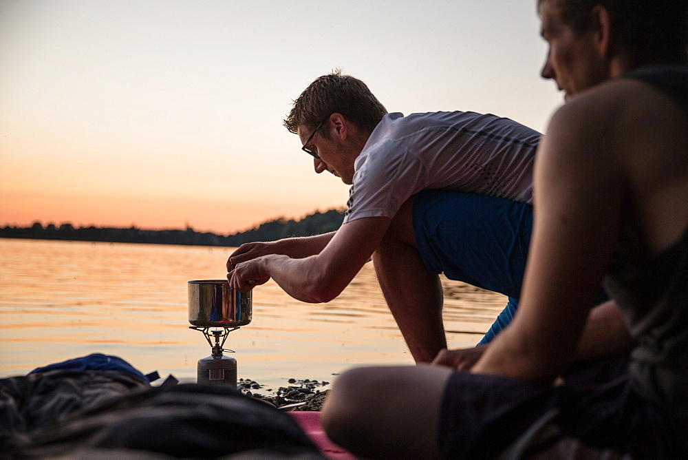 Young man cooking with a camp stove at a lake, Freilassing, Bavaria, Germany - 1113-105166