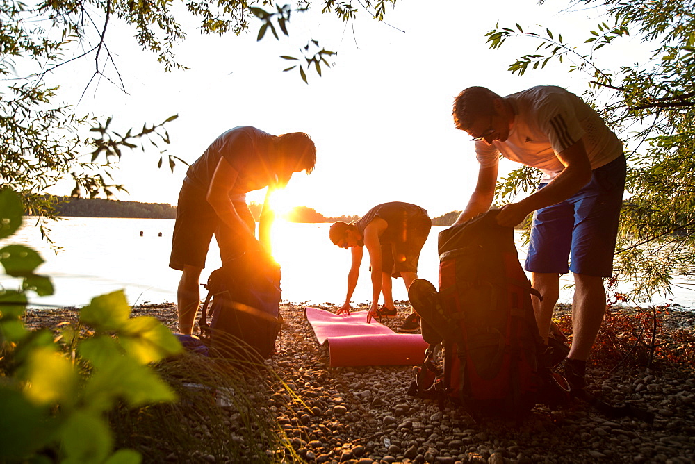Three young male campers preparing their stuff at a lake, Freilassing, Bavaria, Germany - 1113-105167