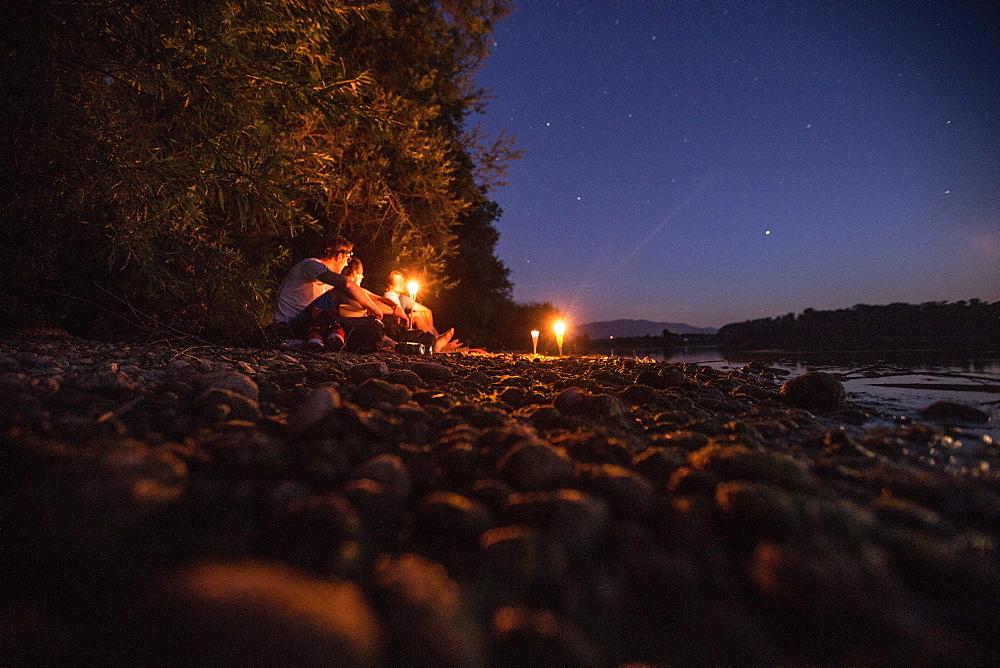 Three young man sitting at a lake at night, Freilassing, Bavaria, Germany - 1113-105174