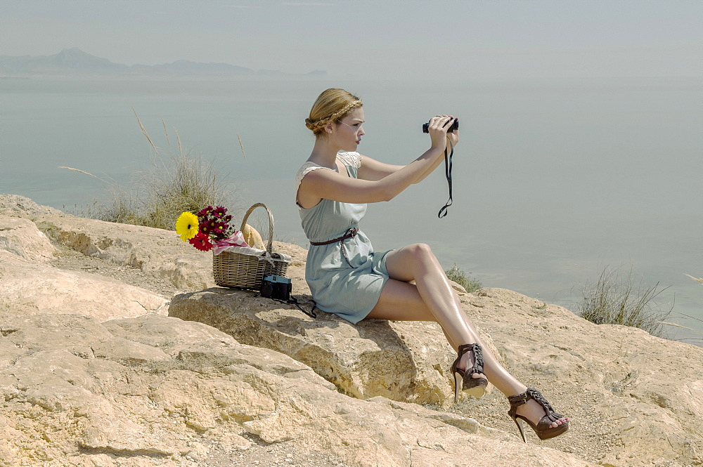 A young woman in stiletto heels sits on a rock with a picnic basket using binoculars on the coast, Spain