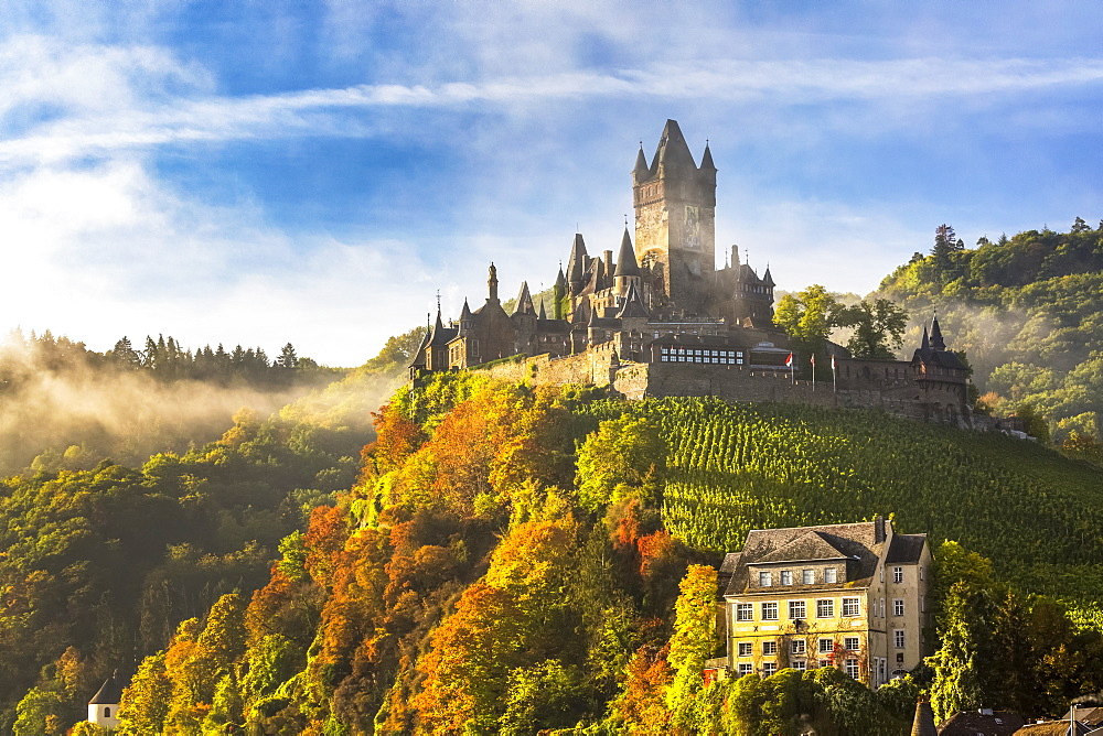Large medieval castle on a colourful treed hillside with fog, blue sky and cloud, Cochem, Germany