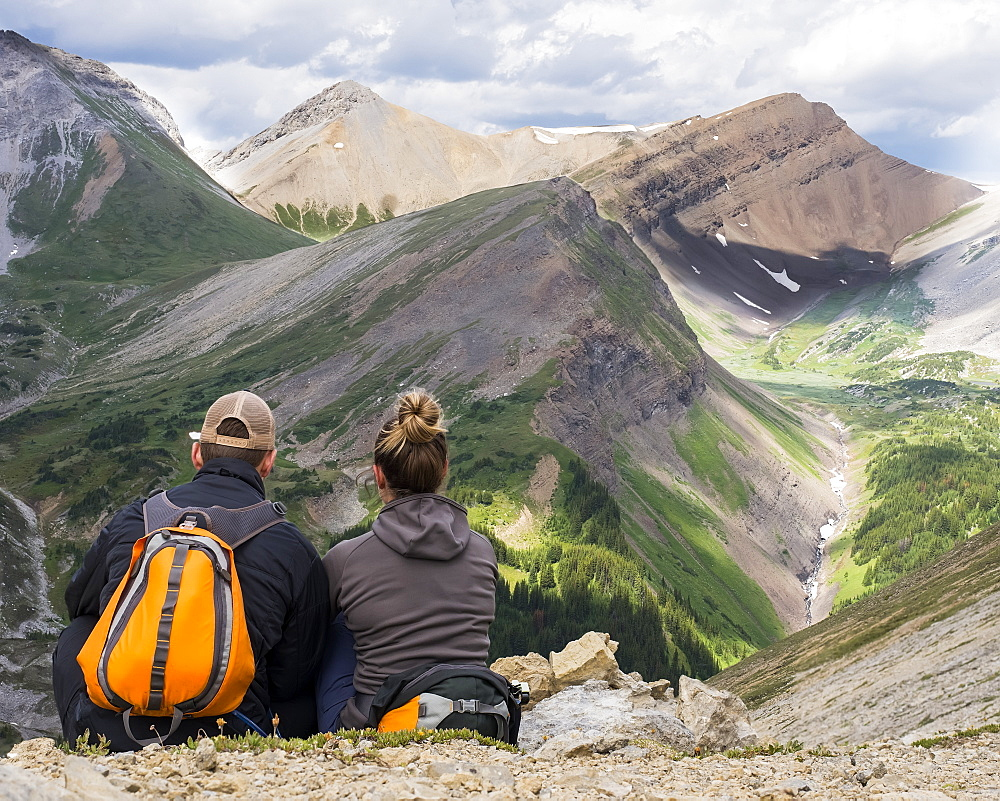 Male and female hiker sitting on a rock ridge overlooking a valley and mountain range in Kananaskis Country, Alberta, Canada