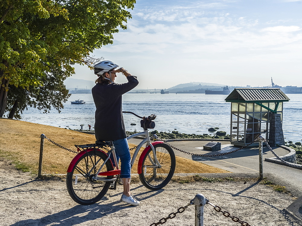 A woman sits on a bike looking out to the ocean and coastline at the Stanley Park Seawall, Vancouver, British Columbia, Canada