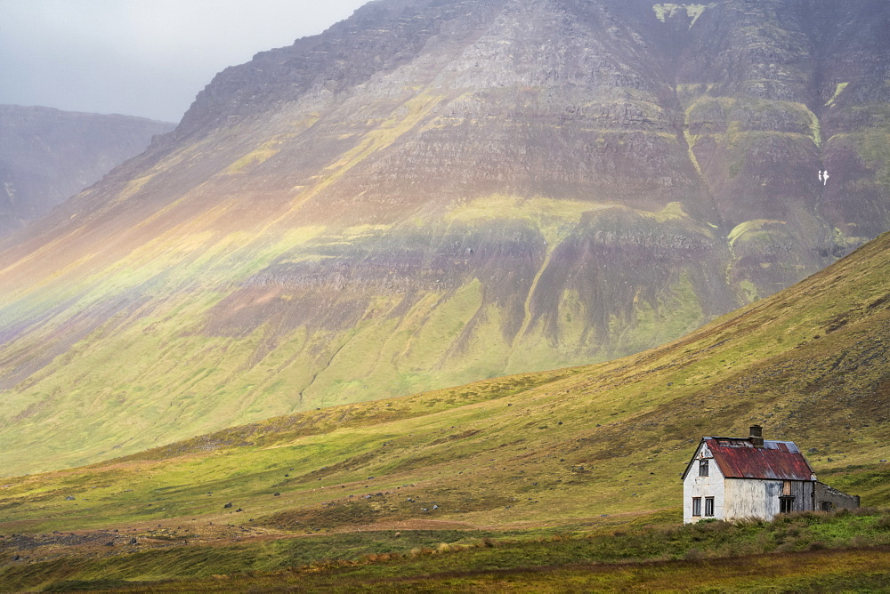 Faint rainbow over an abandoned Iceland homestead, West Fjords, Iceland