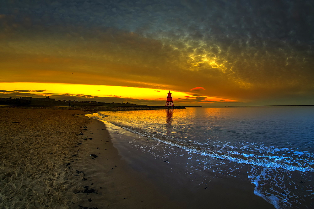 Herd Groyne Lighthouse backlit by a glowing, golden sunset, South Shields, Tyne and Wear, England