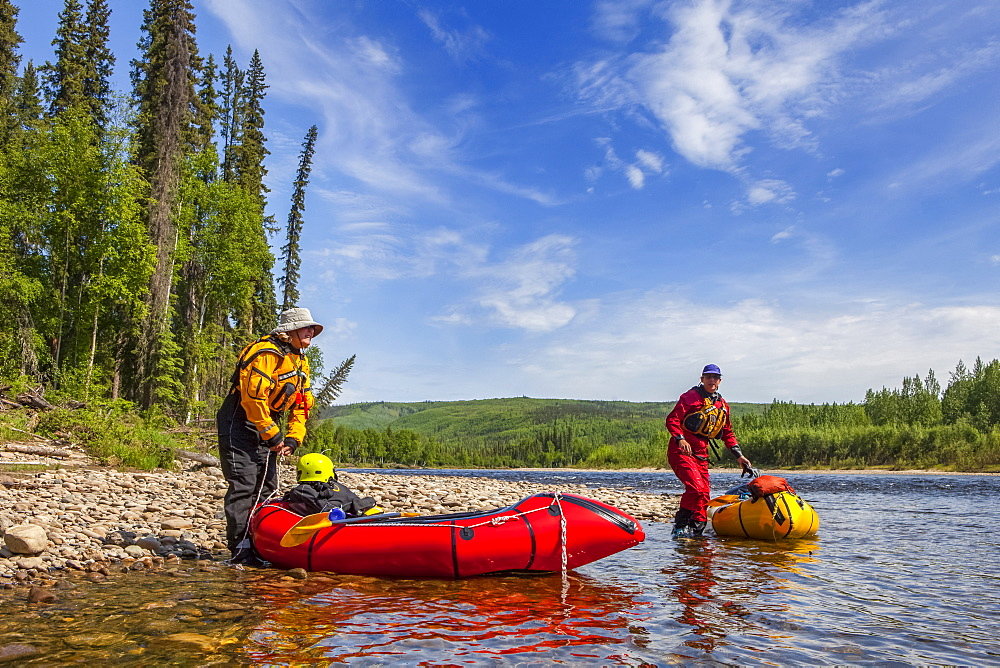 Two women packrafters getting ready to launch on the Charley River in summertime, Yukon–Charley Rivers National Preserve, Alaska, United States of America