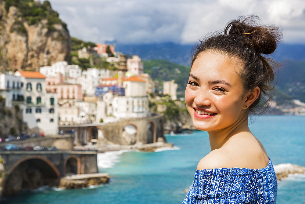 A young woman poses with the view of the Amalfi coastline and the Mediterranean Sea in the background, Amalfi, Italy