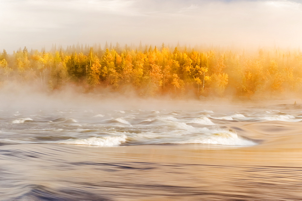 Flowing water with fog settled over a river and autumn coloured forest, Sturgeon Falls, Whiteshell Provincial Park, Manitoba, Canada