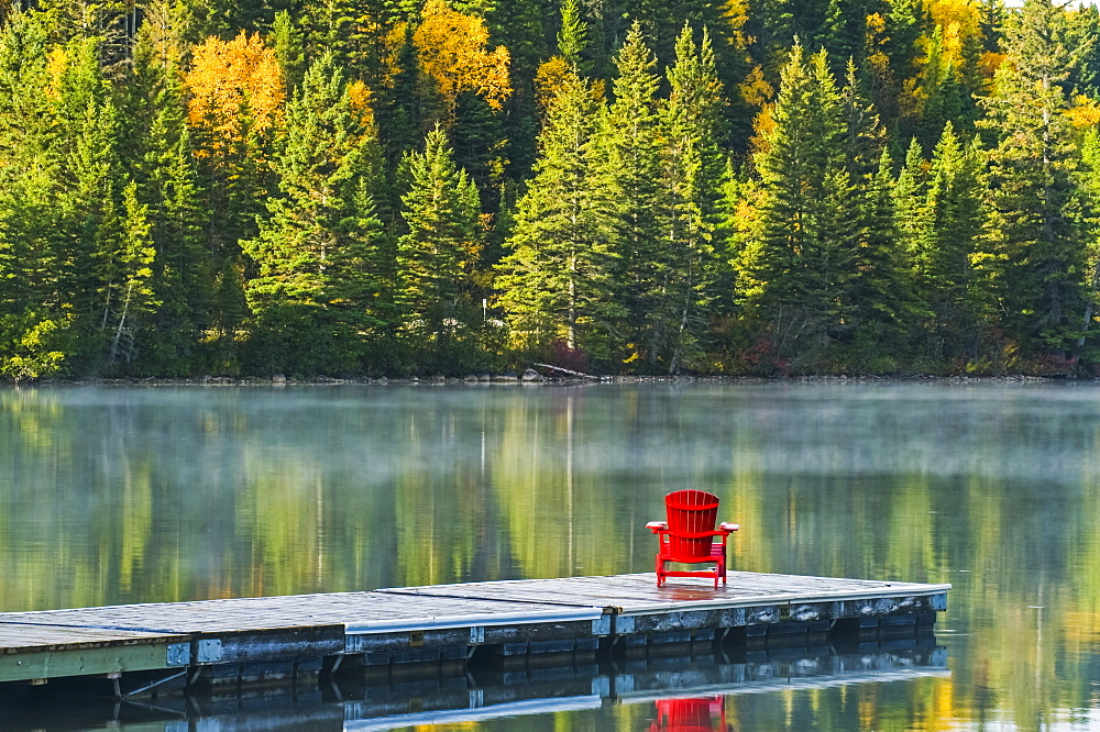 Muskoka chair on dock with autumn coloured foliage reflected in the tranquil lake water of Clear Lake, Riding Mountain National Park, Manitoba, Canada