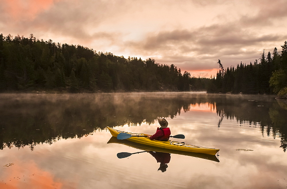 A man kayaking at sunset in the Rushing River, near Kenora, Ontario, Canada