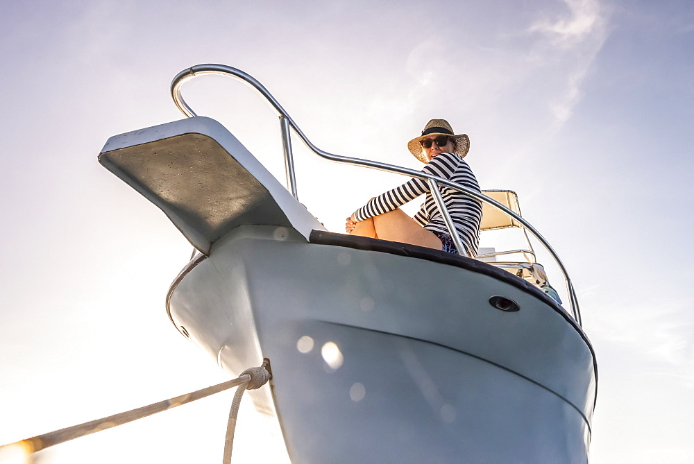 A woman wearing sunglasses and a sun hat looks down at the camera from the deck of a boat against a blue sky with sunlight, Bay Islands Department, Honduras