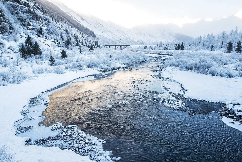 River flowing through a snowy, mountainous landscape at sunrise, Alaska, United States of America