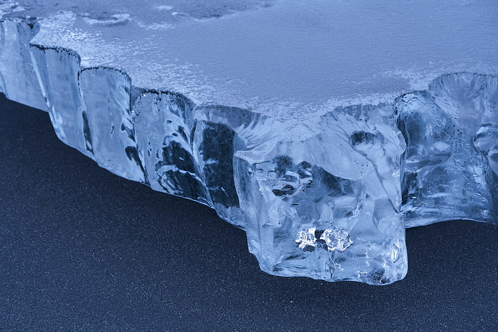 Close-up of a piece of ice sitting in the black sand on the South shore of Iceland, Iceland