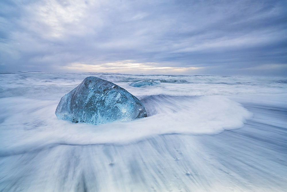 Large ice block laying on the shores of Southern Iceland while waves crash on shore, Iceland