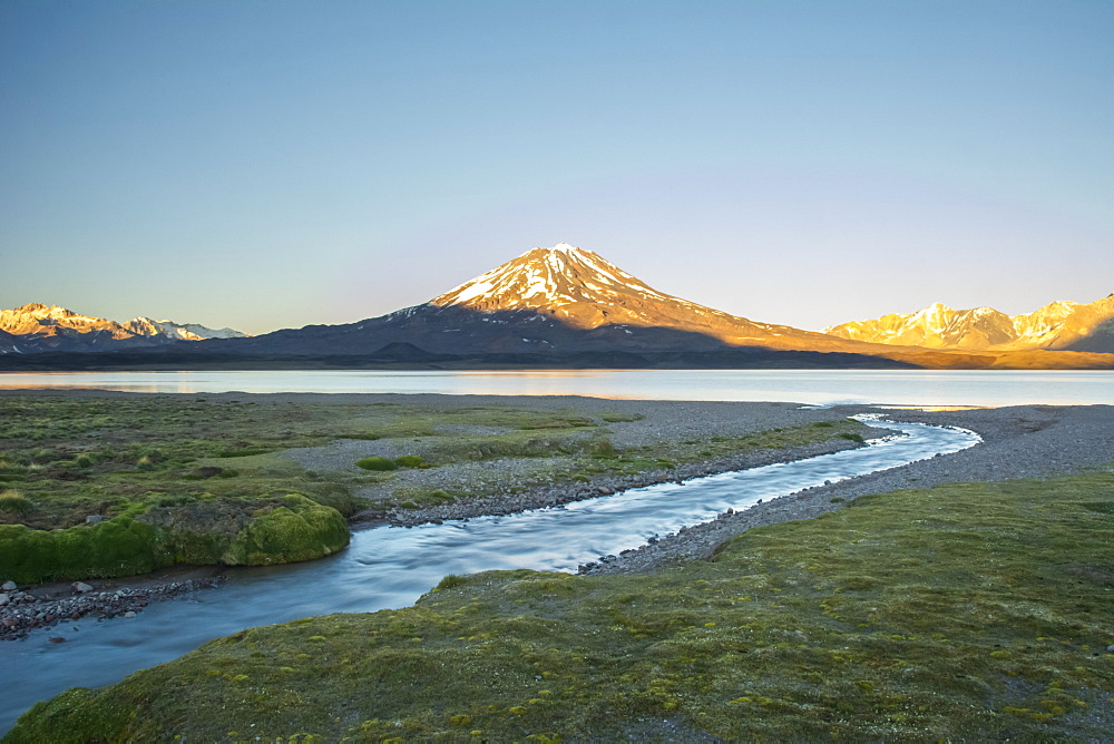 A stream leads the eye towards a high altitude lake. A volcano and snow-capped mountains in the distance are lit by the sunrise against a pure blue sky, Mendoza, Argentina