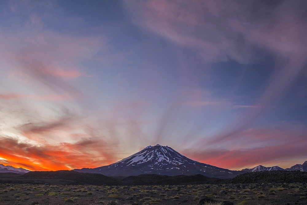 The snow-covered slopes of a volcano are set against a red sunset sky, Mendoza, Argentina
