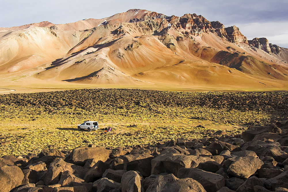 A camper truck is seen parked in the immensity of a high altitude valley in the Andes. The mountains in the distance are ocre-coloured from the late day light, Mendoza, Argentina
