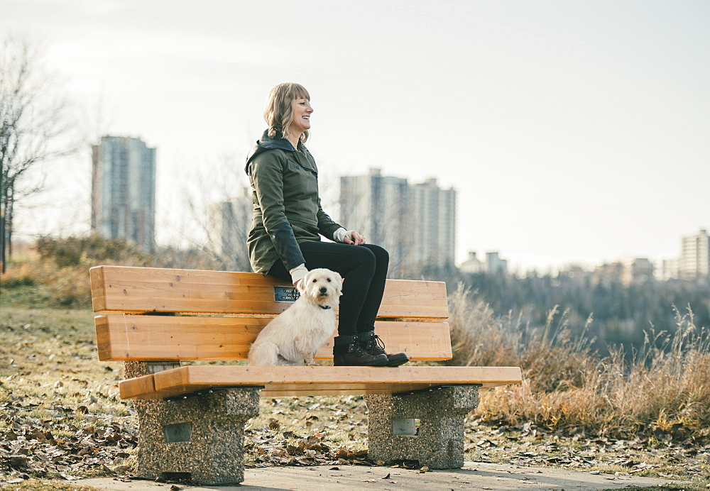 Woman out with her dog with a city skyline in the background, Edmonton, Alberta, Canada