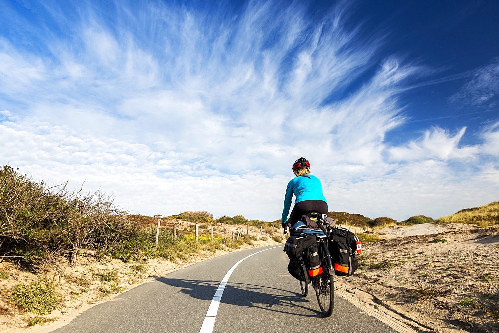Female cyclist on paved bike pathway along rolling sand dunes with dramatic clouds and blue sky, South of Zandvoort, Netherlands