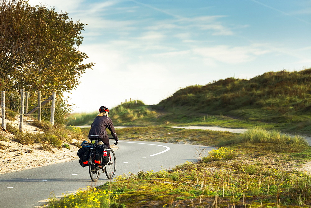 Female cyclist on paved bike pathway along rolling sand dunes and grassy hills, South of Zandvoort, Netherlands