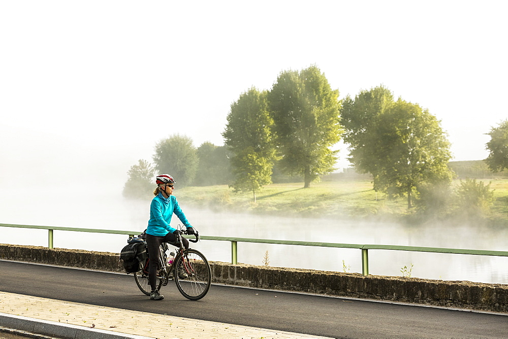 Female cyclist along river pathway with mist in the river valley looking over trees along river bank, North of Remich, Luxembourg