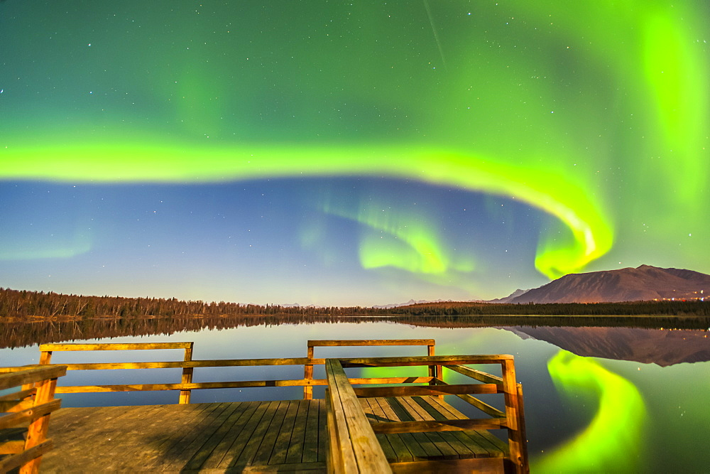 The Northern Lights are seen reflecting off Beach Lake on a clear, autumn night with a wooden dock in the foreground, Chugiak, Alaska, United States of America
