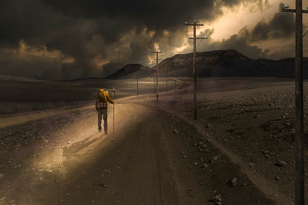 A man walks along an empty road in a sunbeam shining through dark clouds, composite image