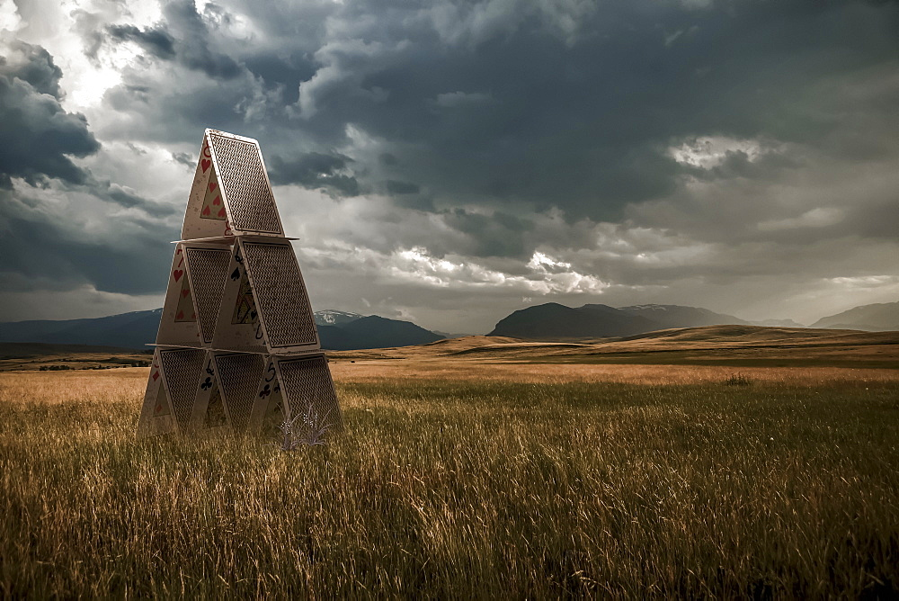 Playing cards set up in a grass field under a stormy sky, composite image