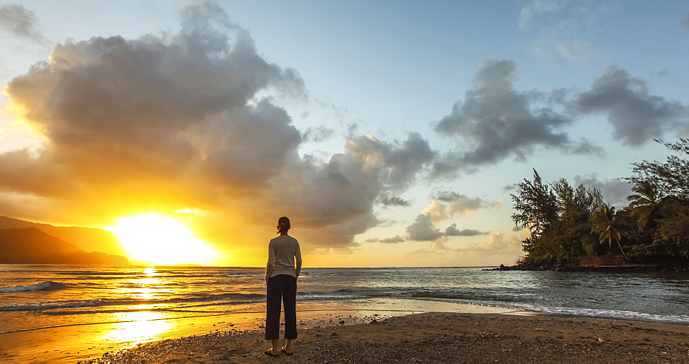 Woman standing on the beach at sunset, Kauai, Hawaii, United States of America