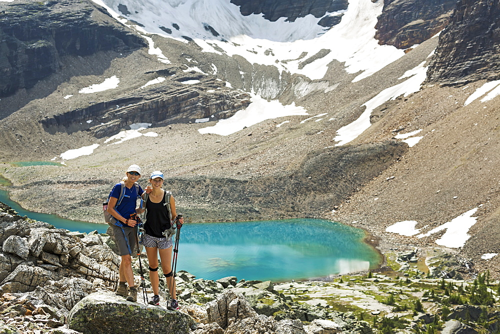 Two female hikers standing in a large rocky area with a colourful alpine lake and mountain cliffs with snow in the background, British Columbia, Canada