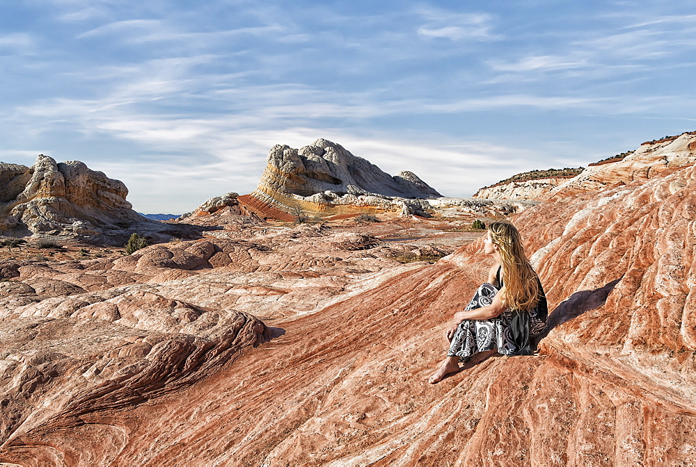A woman sits on a rock formation enjoying the view at White Pocket, Vermilion Cliffs National Monument, Kanab, Arizona, United States of America