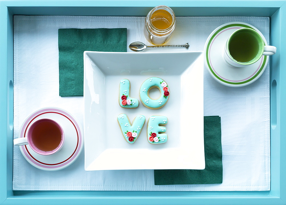 Tea in cups with saucers and cookies spelling out love on a tray