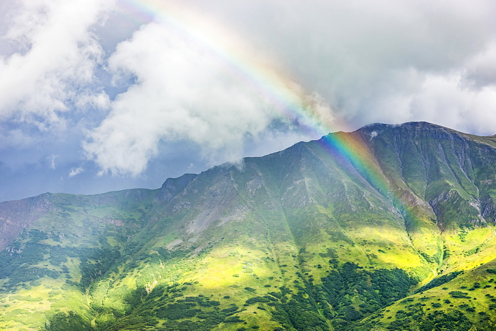 A rainbow shines through atmospheric light, lush green mountainsides in the background, Hatcher Pass, South-central Alaska, Palmer, Alaska, United States of America