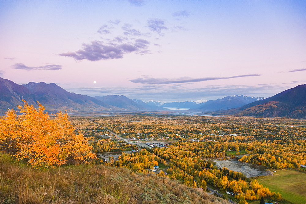 View of the moon rising above Palmer and the Knik River from atop the Butte, the Chugach Mountains in the background during twilight on a clear evening, South-central Alaska, Palmer, Alaska, United States of America