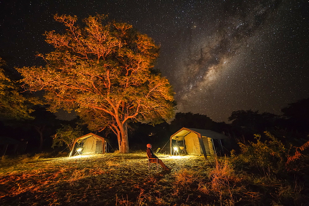 The milky way in the sky with a tents below in a bush camp as a man sits looking up at the sky, Botswana