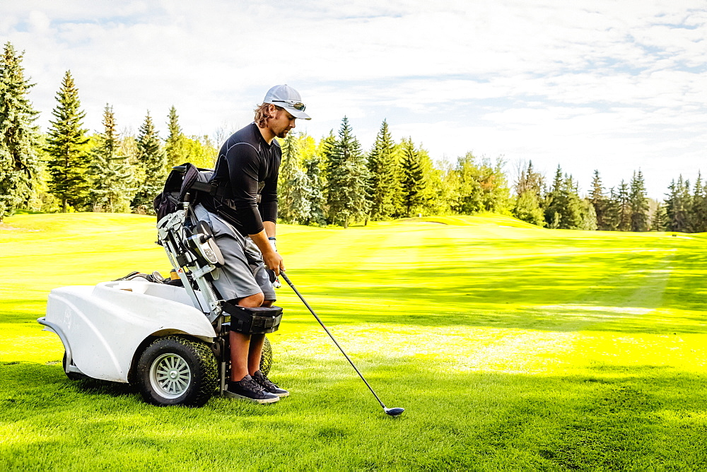 A physically disabled golfer using a specialized wheelchair lines up his driver with the ball on the golf green, Edmonton, Alberta, Canada