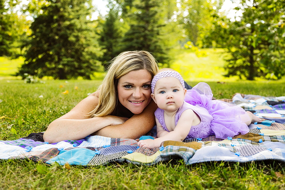 A mother and her baby daughter laying on a picnic blanket and posing for the camera while enjoying a family outing in a city park on a warm fall afternoon, Edmonton, Alberta, Canada