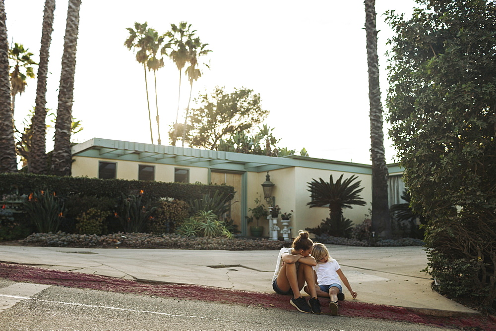 Two young girls sit on a street curb outside a house, Los Angeles, California, United States of America