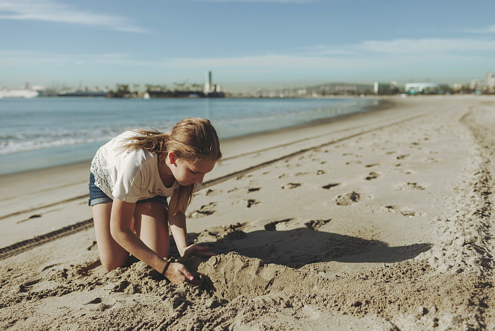 A girl playing in the sand at the beach, Long Beach, California, United States of America