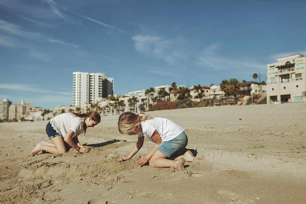 Two girls playing in the sand at the beach with condominium buildings in the background, Long Beach, California, United States of America