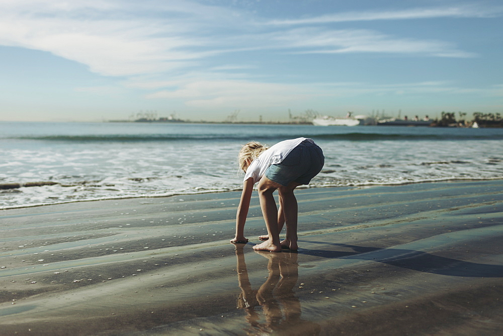 A young girl plays in the wet sand along the shoreline, Long Beach, California, United States of America - 1116-48149