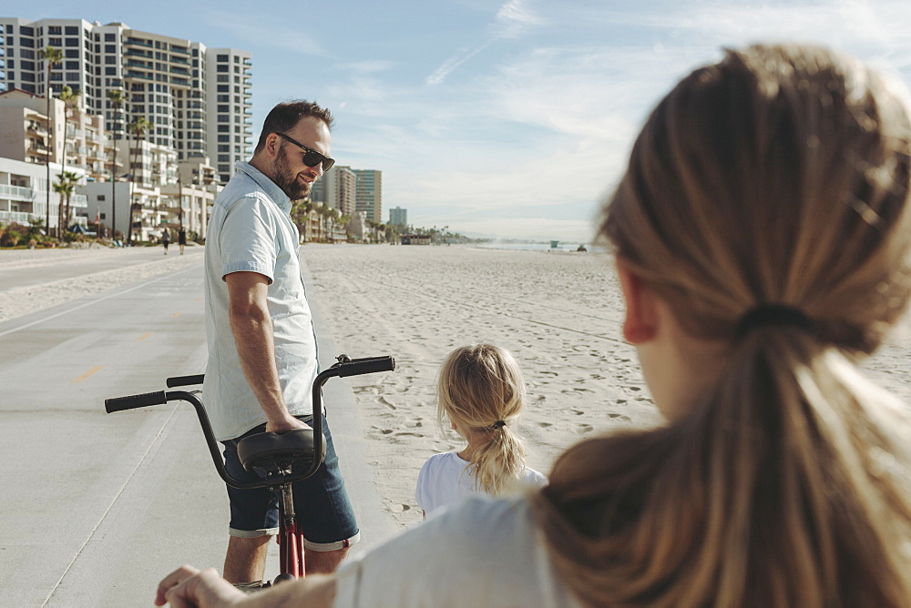 A father and daughters riding bikes at Long Beach, Los Angeles, California, United States of America
